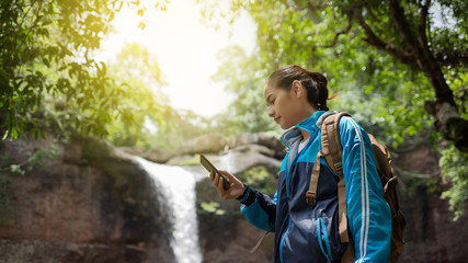 Asian women Use the phone during a trip to the forest and waterfall.