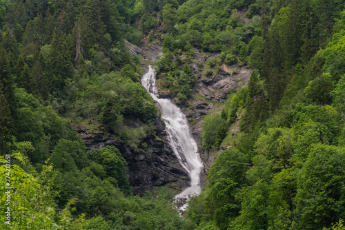 Wall mural landscape view of a high picturesque waterfall in lush green forest landscape
