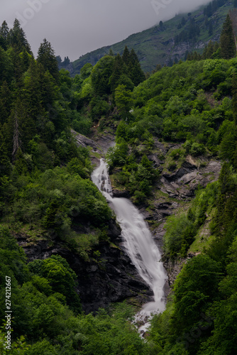 Wall mural vertical view of a high picturesque waterfall in lush green forest landscape
