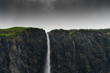 Fotomurales - high waterfall plummets off a rock and grass cliff in the Swiss Alps