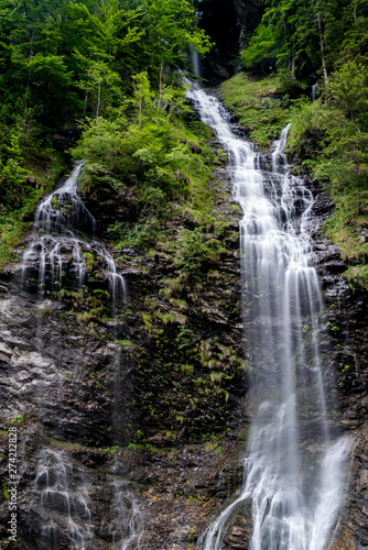 Wall mural panorama of high picturesque waterfall in lush green forest landscape