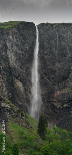 Wall mural high waterfall plummets off a rock and grass cliff in the Swiss Alps