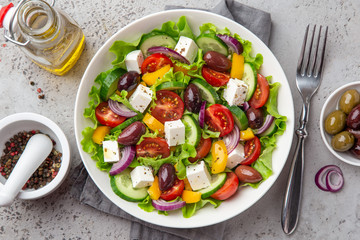 fresh greek salad ( tomato, cucumber, bel pepper, olives  and feta cheese) in white bowl
