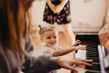 beautiful little girl with tails on head charismatic singing the song at the piano which plays mom. Selective focus, noise effect