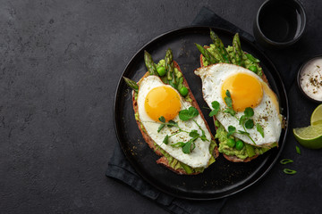 toasts with avocado, asparagus and fried egg on black plate