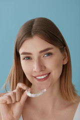 Teeth whitening. Woman with healthy teeth using removable braces