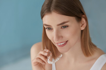 Dental care. Smiling woman using removable clear teeth braces.