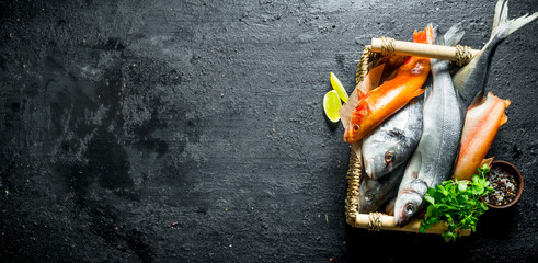 Raw fish on tray with parsley and lime slices. Wall mural