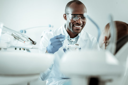 Dark-skinned joyful doctor carrying toothbrush and model of jaw