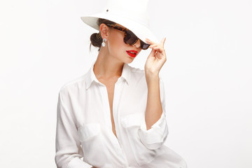 Beautiful girl in an elegant white hat, sunglassess and exquisite jewelry.