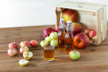 fruits, food and harvest concept - glass and bottles of apple juice or cider on wooden table