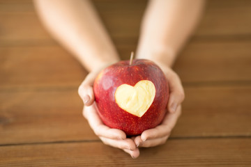 food, valentines day and health concept - close up of hands holding ripe red apple with carved...