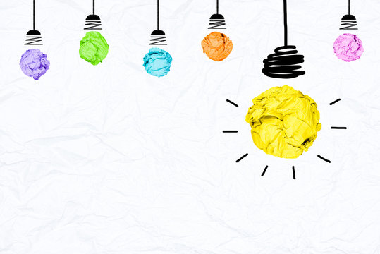 Colorful paper light bulb on wrinkled paper texture with copy space