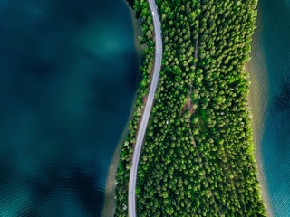 Fototapeta Aerial view of road between green forest and blue lake in Finland