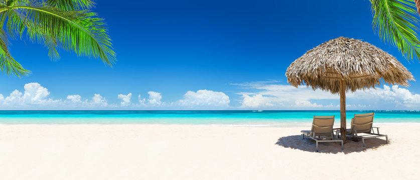 Beach chairs with umbrella and beautiful sand beach.