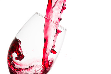 Close up of the wave formed on the pouring of red wine on a tasting glass against a white background
