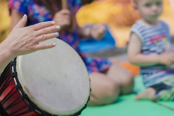 The girl plays the Djembe drum for children