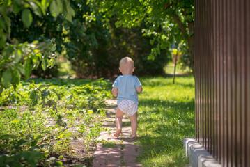 Little baby in a diaper in the garden