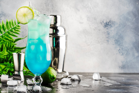 Blue Hawaii or Blue Lagoon - summer alcoholic cocktail with vodka, liqueur, tonic, pineapple juice and ice, in high Hurricane glass, selective focus
