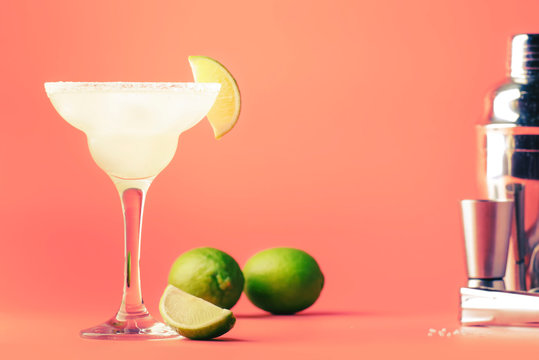 Lime margarita alcoholic cocktail with silver tequila, liqueur, lime juice, sugar syrup, salt and ice, festive trendy pink background, copy space