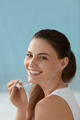 Dental care. Smiling woman with white smile using whitening tray