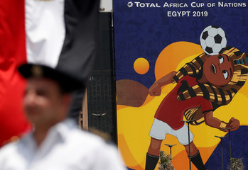 """A police officer stands guard near the national flag and a picture of a mascot named """"TUT"""", at the Cairo International Stadium ahead of the Africa Cup of Nations opening in Cairo"""