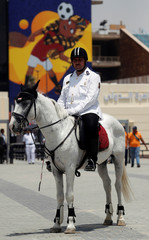 """A police officer sits on a horse near a picture of a mascot named """"TUT"""", at the Cairo International Stadium ahead of the Africa Cup of Nations opening in Cairo"""