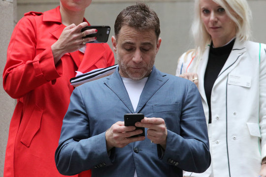 The Slack Technologies Inc. CEO Butterfield looks at mobile phone during company's direct listing at the New York Stock Exchange (NYSE) in New York