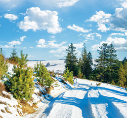snow covered country road in mountains. beautiful sunny day with fluffy clouds on a blue sky. spruce tree along the path. wonderful winter scenery