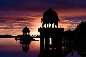 Fototapete - Silhouettes of gazebos while sunset at Gadisar Lake, Jaisalmer, Rajasthan, India