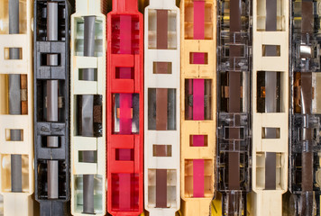 stack of old retro cassette tapes with tape ends showing on yellow background