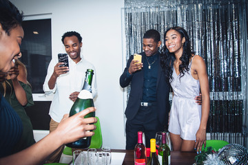 Friends taking photos with smart phones at party