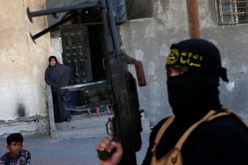 Palestinian woman looks on as an Islamic Jihad militant takes part in an anti-Israel military show at Al-Shati refugee camp in Gaza City