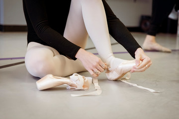 Low section of ballerina wearing ballet shoes while sitting on floor in dance studio