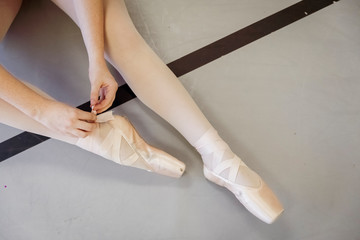 Low section of ballerina wearing ballet shoes while sitting on floor in studio