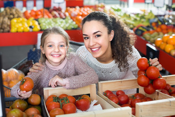 Woman and little girl buying tomatoes .