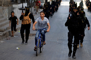 Palestinian rides a bicycle as Islamic Jihad militants take part in an anti-Israel military show at Al-Shati refugee camp in Gaza City