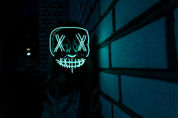 A man in a glowing blue mask at night near a white brick wall. The concept of shooting horror, carnivals, Halloween