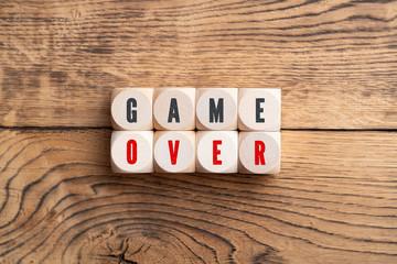 """Würfel mit Aufschrift """"GAME OVER"""" auf Holz-Hintergrund"""