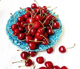 Red ripe cherries on a blue plate ready to eat