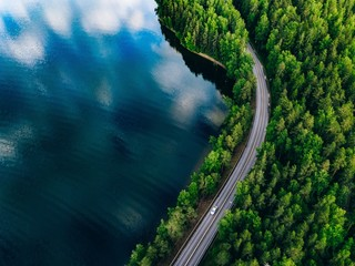 Aerial view of road between green forest and blue lake in Finland Wall mural