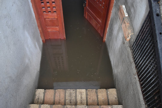 Flooded basement after the massive rain. Flooded cellar with wooden door full of dirty water.