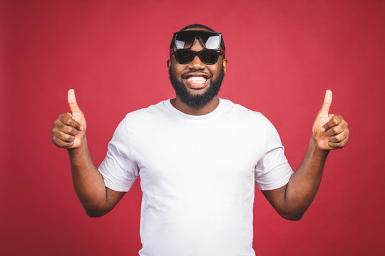 Funny guy in white t-shirt and sun glases jumping and looking at camera. Studio portrait of emotional african male model posing on red background. Thumbs up.