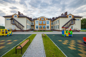 New modern two-storied kindergarten preschool building with big windows on green grassy lawn and blue sky copy space background. Architecture and development concept. Fototapete