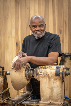 An African American older man creates works of art through bowl turning on a lathe. This shows him working and standing by the machine.