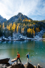 Two men with packs hike and scramble amidst fall colors near Colchuck Lake in the Cascade Range of Washington State.