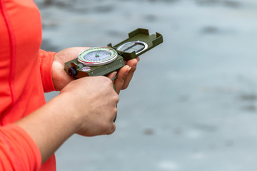 Hands of a woman in the outdoors using a compass to navigate