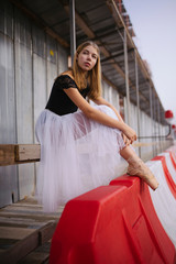 Woman ballerina in the city stands sitting on the railing