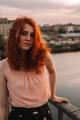 Portrait of young woman with red hair standing by railing on bridge