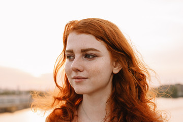 Close up portrait of young woman with red hair and freckles